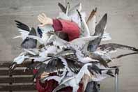 Banksy-Dismaland: una mujer sentada en un banco es atacada por palomas.