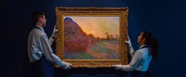 """Dos operarios de Sotheby's con la obra """"Meules"""" de Monet, subastada en Nueva York y que alcanzó la cifra histórica de 110 millones de dólares, 99 millones de euros al cambio. Imagen: Sotheby's / Vídeo: Reuters-Quality."""